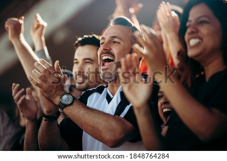 Group of men and women cheering their national team. Football team supporters enjoying during watching a live match from stadium. Royalty-Free Stock Photo #1848764284