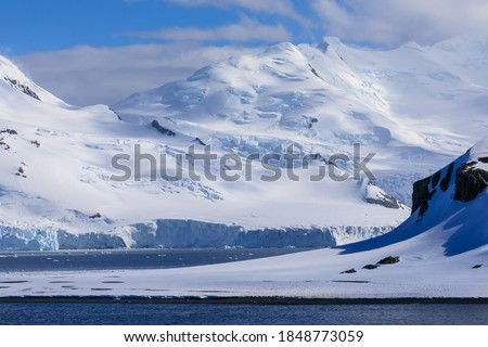 Jaw dropping icy Antarctic scenery of low lying Half Moon Island, with  Livingston Island mountains and glaciers behind, lit by evening sun, South Shetland Islands, Antarctica Royalty-Free Stock Photo #1848773059