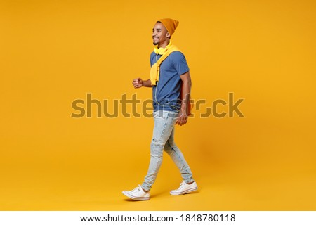 Full length side view of smiling cheerful handsome funny young african american man 20s in blue t-shirt hat walking going looking aside isolated on bright yellow colour background, studio portrait Royalty-Free Stock Photo #1848780118