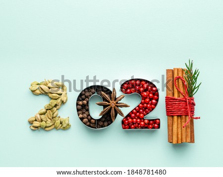 2021 concept. New year 2021 numbers made of spices (cardamom seeds, black peppers, red or pink pepper, anise star and sinnamon sticks wrapped with knit). Mint paper background. Top view. Copy space. #1848781480