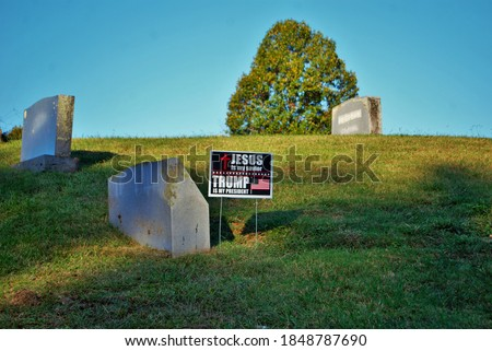 Trump yard sign next to a headstone in cemetery jesus is my savior trump is my president
