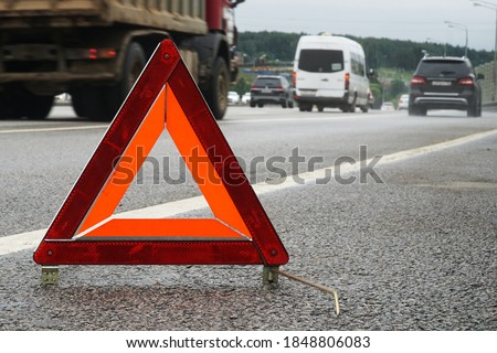 A warning road sign for an emergency stop stands on the asphalt against the background of moving cars.                                Royalty-Free Stock Photo #1848806083