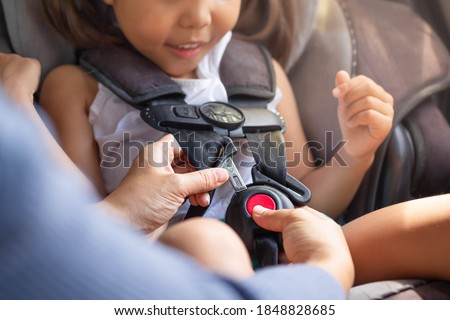 Parent buckling her child's seat belt in the car. Transportation safety. Royalty-Free Stock Photo #1848828685