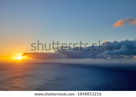 Sunset over the ocean. View from the westernmost point of the island of Madeira, Ponta do Pargo lighthouse. Quiet moment. Traveling around the island of Madeira in Portugal. Royalty-Free Stock Photo #1848853216