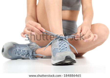Runner fitness woman tying the shoelaces ready to sport isolated on a white background                 #184886465