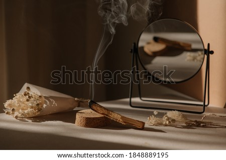 palo santo with jet of smoke, mirror and dried flowers on a neutral background. Abstract trendy picture. Minimalistic wabi sabi style. Royalty-Free Stock Photo #1848889195