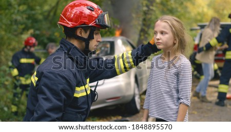 Fireman checking injures of cute girl then handing kid to worried mother near burning car after accident in countryside