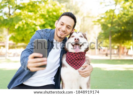 Front view of a good looking man in his 30s taking a photo with his beautiful dog wearing a bandana in the grass at the park