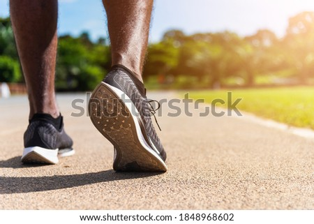 Asian young athlete sport runner black man wear feet active ready to running training at the outdoor on the treadmill line road for a step forward, healthy exercise workout, closeup back shoe Royalty-Free Stock Photo #1848968602