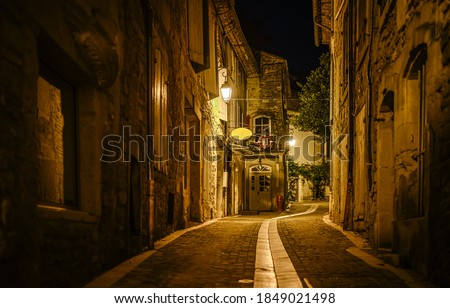 Old narrow paved street in night european town. Narrow paved street. Night narrow pave street view. Paved street at night #1849021498
