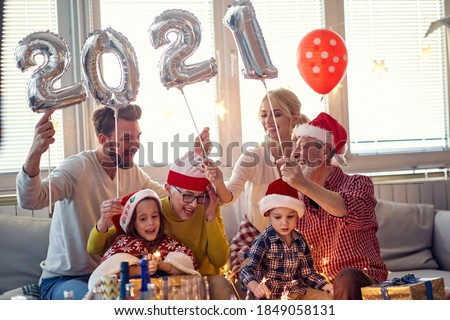 Cheerful family looking forward New Year presents in festive home atmosphere. New Year, holiday, family time together #1849058131