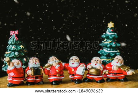 Santa claus sing a song on Christmas caroling day or Carolers singing with snows.Group of Santa claus play music sing carol song on celebration of christmas day party in winter.Celebration Holidays.