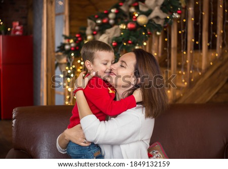 Cheerful happy mom and little son 4 years old on background of wooden house beautifully decorated before Christmas hug each other.  Cozy Christmas atmosphere Royalty-Free Stock Photo #1849132159