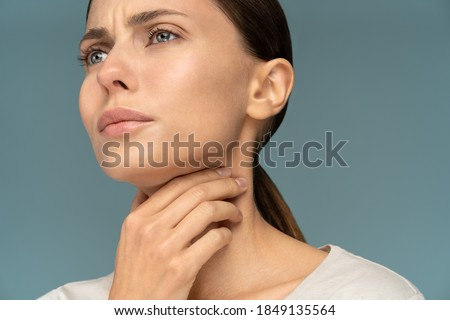 Closeup of sick woman having sore throat, tonsillitis, feeling sick, caught cold, suffering from painful swallowing, strong pain in throat, holding hand on her neck, isolated on studio blue background Royalty-Free Stock Photo #1849135564