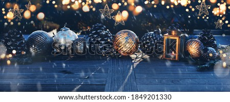 Christmas decoration on a wooden table in darkness with golden bokeh and snowflakes. Background for christmas and advent concepts with space for text. Royalty-Free Stock Photo #1849201330