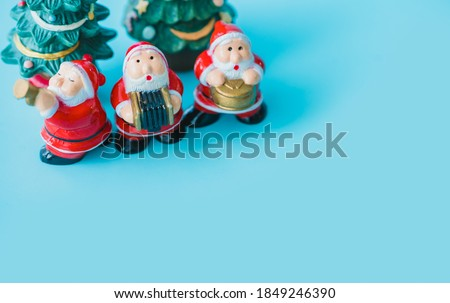 Flat lay Santa sing a song on Christmas caroling day Carolers singing with snows.Group of Santa claus play music singing carol song on celebration of christmas day in winter time.Holidays music.blue.