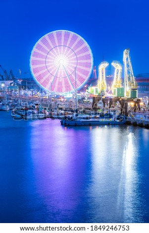 Ships, cranes  and amusement park at Odra River Boulevards in Szczecin. Crowds enjoying Days of the Sea. Long exposure night photo Royalty-Free Stock Photo #1849246753
