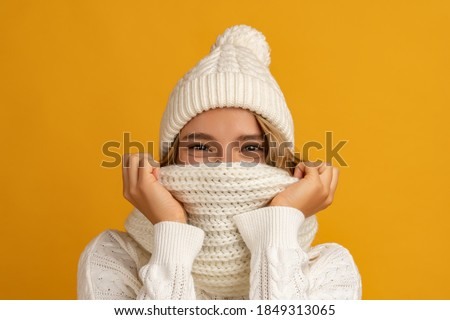 young smiling happy pretty blond woman wearing white knitted sweater, scarf and hat, warm winter cold season fashion accessories trend, posing on yellow studio background isolated Royalty-Free Stock Photo #1849313065