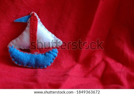 A blue ship with a white sail and a blue flag, on a red background. Felt decorations, unique sweet and handmade.
