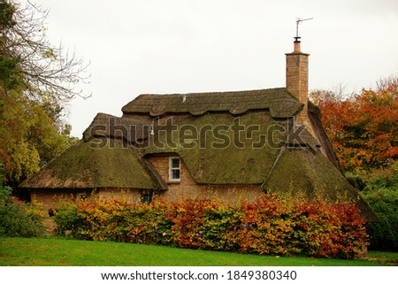 Quintessentially English thatched cottage in Gloucestershire England on a cloudy fall day. Traditional building, thatching is the craft of building a roof with dry vegetation like straw or water reed. Royalty-Free Stock Photo #1849380340