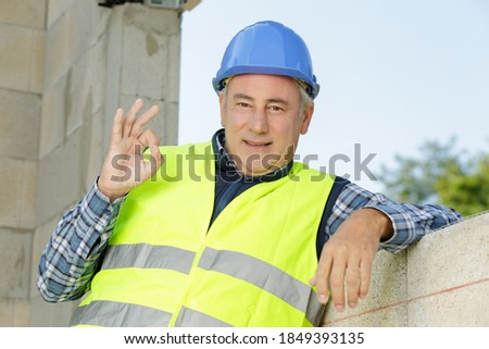 mature workman making ok sign on unfocused background