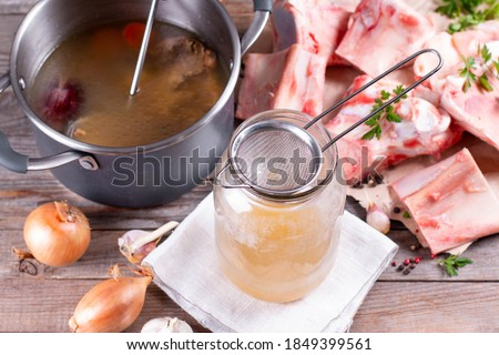 Passing the bone broth through a sieve. Concentrated Bone Broth in a Glass Jar Royalty-Free Stock Photo #1849399561