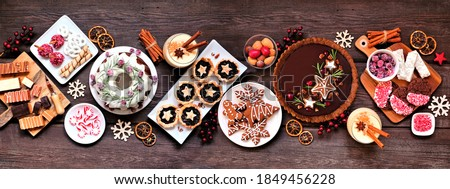 Assorted Christmas holiday desserts and sweets. Top view panoramic table scene over a rustic wood background. Bundt cake, chocolate pie, mincemeat tarts, cookies, fudge and eggnog. #1849456228