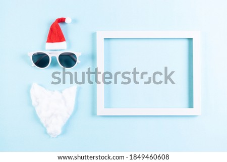 Creative christmas composition. Greeting card, invitation. Picture frame, santa hat, beard and glasses on pastel blue background with copy space. top view.