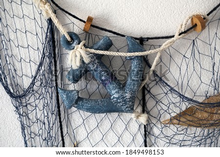 A closeup shot of an anchor and a fishing net on the wall of a house