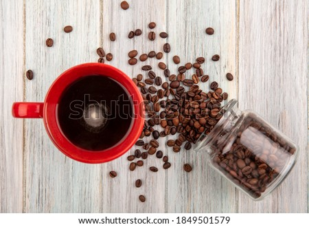 top view of cup of coffee and coffee beans spilling out of glass jar on wooden background #1849501579