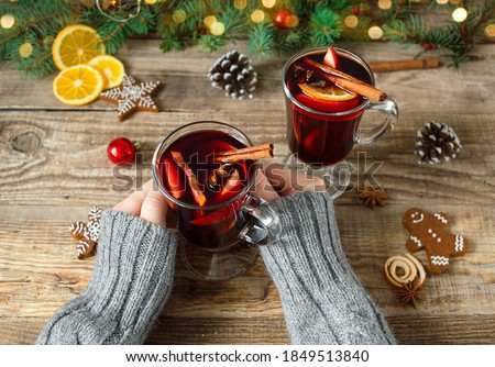 Top view of women holding glasses with Christmas hot mulled wine red with spices on a wooden background with fir branches and Christmas decor. New year's drinks.Traditional hot drink . #1849513840