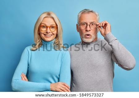 Cheerful middle aged woman and her husband pensioner reacts on shocking news keeps hand on spectacles isolated over blue background. Family age and emotions concept. Senior couple at pose home Royalty-Free Stock Photo #1849573327