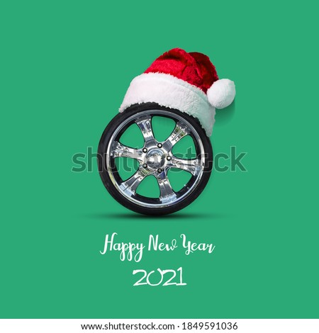 Car wheel in the hat of Santa Claus, on a green background. Congratulations to the car repair shop, car shop. Festive background.