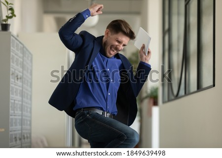 Wish come true. Euphoric happy male executive employee manager worker jumping dancing at office hallway screaming in delight getting career salary growth, finding hard solution, receiving job of dream Royalty-Free Stock Photo #1849639498