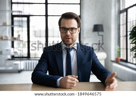 Front view young male executive manager in formal wear holding negotiations meeting with colleagues, discussing working issues or giving professional consultation to clients online in modern office. Royalty-Free Stock Photo #1849646575