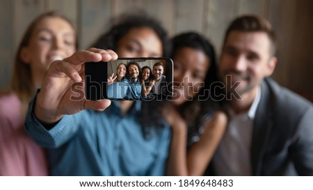 Taking group selfie. Blurred portrait of four diverse multiethnic millennial friends students coworkers hugging smiling and looking at camera showing spectator self picture making on smartphone webcam