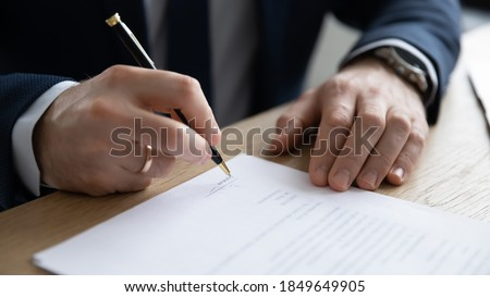 Close up young entrepreneur signing paper contract or business legal agreement, sitting at table. Focused male ceo executive manager putting signature on company financial or law document in office. Royalty-Free Stock Photo #1849649905