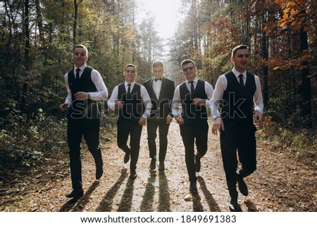 Cheerful, young, energetic witnesses of the groom next to the groom. Friends congratulate the groom.  Royalty-Free Stock Photo #1849691383