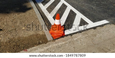 Orange cone road sign on the asphalt. A cone on the road. Warning for drivers. Limiter for cars