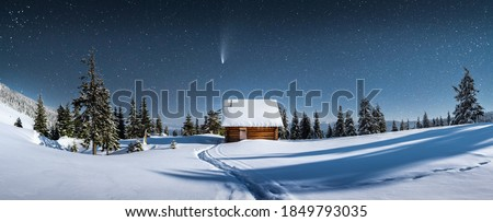 Fantastic winter landscape panorama with wooden house in snowy mountains. Starry sky with Milky Way and snow covered hut. Christmas holiday and winter vacations concept Royalty-Free Stock Photo #1849793035