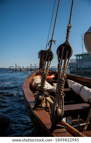 Rigging and ropes on an old sailing ship for summer sailing. Ropes on the boat. Rook, close-up overlooking the lake or sea. Sailing boat pulley, block and tackle with moored nautical rope. Royalty-Free Stock Photo #1849822945