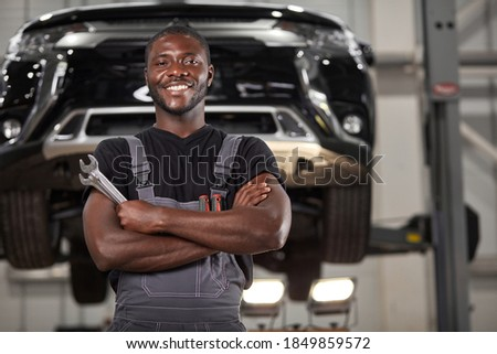 portrait of positive afro american auto mechanic in uniform posing after work, he is keen on repairing cars, automobiles. Royalty-Free Stock Photo #1849859572
