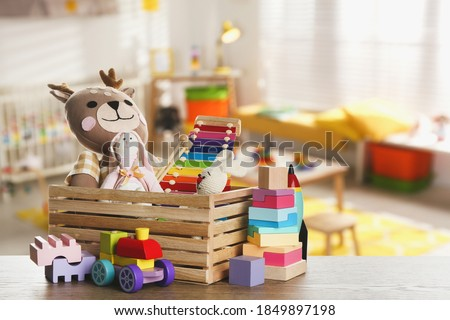 Set of different cute toys on wooden table in children's room Royalty-Free Stock Photo #1849897198