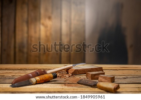 Craftsman carving tools with a chisel  carving knife a piece of dark wood on carpentry workbench  Royalty-Free Stock Photo #1849905961
