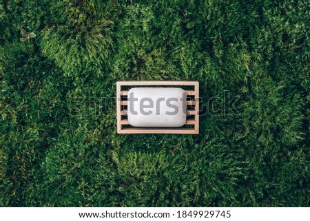 Handmade shampoo, soap bar on wooden dish over green moss texture. Copy space. Top view. Zero waste, eco friendly product, natural organic bathroom tool. Ecological skin care, body treatment concept. Royalty-Free Stock Photo #1849929745
