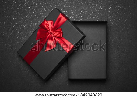 Opened black gift box with a red ribbon and a large bow on a dark granite surface. Empty box. Mockup Royalty-Free Stock Photo #1849940620
