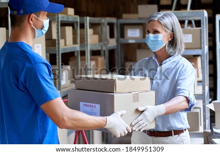 Female manager supervisor wearing face mask preparing fast drop shipping safe delivery giving parcels packages boxes to male courier taking ecommerce orders to deliver standing in warehouse storage. Royalty-Free Stock Photo #1849951309