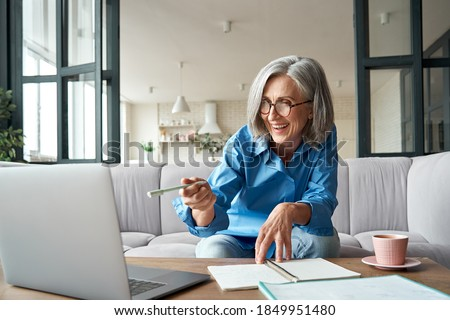 Happy mature older woman video calling on laptop working from home. Smiling 60s middle aged businesswoman talking by conference online virtual chat using computer at home office sitting on couch. Royalty-Free Stock Photo #1849951480