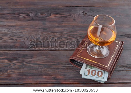 Glass of cognac on a wallet. Money loss and alcohol concept. Brown wooden table. Royalty-Free Stock Photo #1850023633