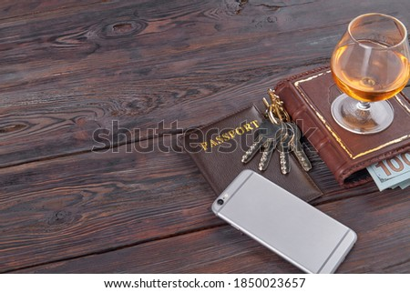 Top view businessmans belongings on wood. Glass of cognac on a book and passport. Royalty-Free Stock Photo #1850023657